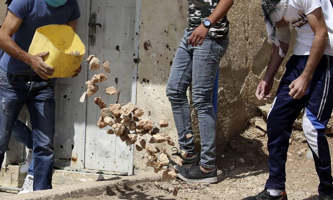 Manifestantes palestinos coletam pedras para atirar contra as forças israelenses durante uma manifestação semanal contra a expropriação de terras palestinas por Israel na aldeia de Kfar Qaddum, perto de Nablus, na Cisjordânia ocupada JAAFAR ASHTIYEH / AFP