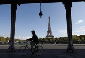 Homem passa de bicicleta em frente à Torre Eiffel: incentivo ao meio de transporte Foto: GONZALO FUENTES / REUTERS