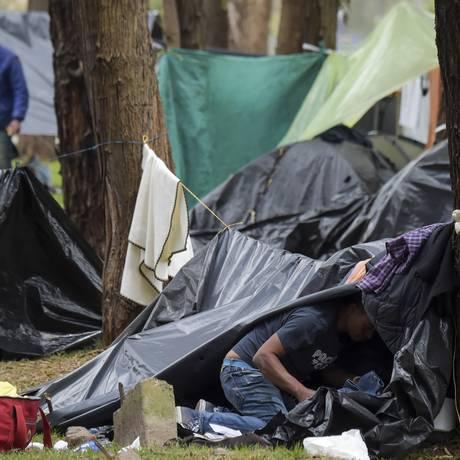 Imigrantes venezuelanos alojados em acampamento improvisado ao lado da rodoviária de Bogotá Foto: RAUL ARBOLEDA / AFP