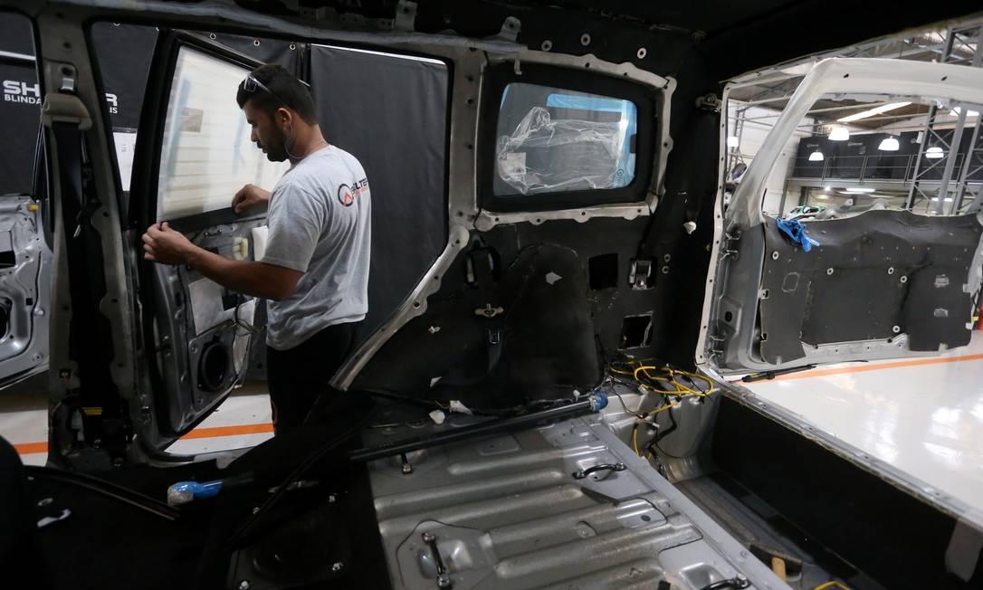 Técnico trabalha na blindagem de um veículo; atividade tem crescido a reboque da violência disseminada no estado Foto: Fabiano Rocha / Agência O Globo