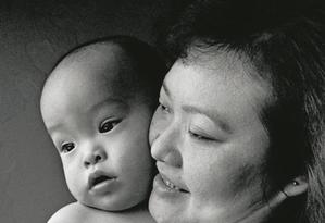 A vietnamita Kim Phuc Phan Thi com seu filho Thomas, em 1994, no Canadá, onde vive. Ela passou por 17 cirurgias para tratar as queimaduras de napalm Foto: Anne Bayn / Divulgação