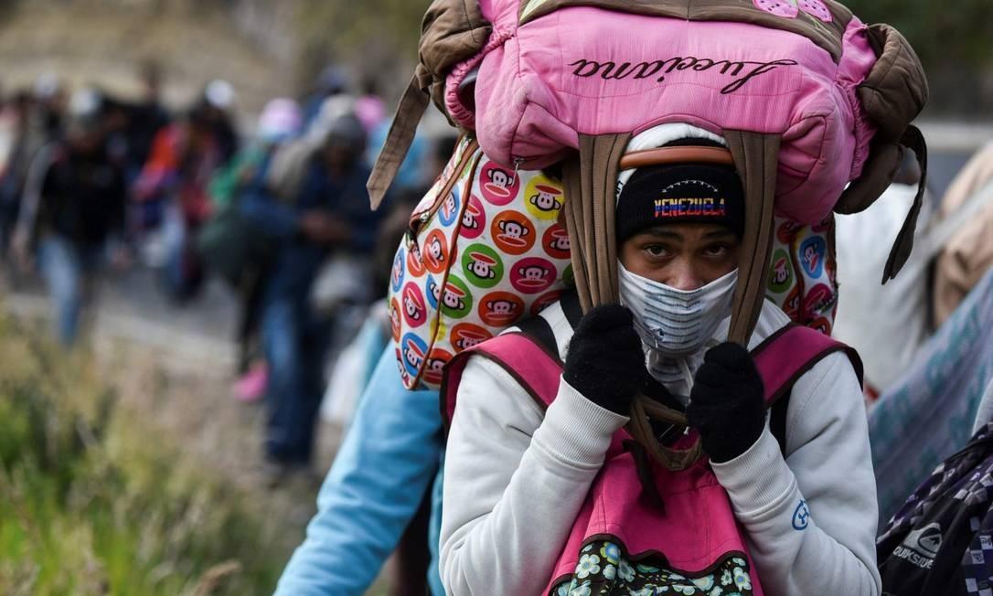 Imigrante venezuelana carrega malas enquanto atravessa estrada no Equador para chegar ao Peru Foto: LUIS ROBAYO / AFP