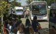 Passageiros na pista entre ônibus e vans Foto: Gabriel de Paiva / Agência O Globo