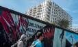 Com mais de cem painéis coloridos, a East Side Gallery cobre 1,3km do antigo Muro de Berlim e recebe cerca de três milhões de visitantes por ano Foto: JOHN MACDOUGALL / AFP