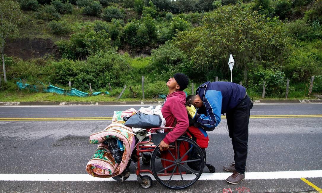 José Agustín Lopez e seu filho viajam com a cadeira de rodas até a Colômbia em busca de remédios Foto: SCHNEYDER MENDOZA / AFP