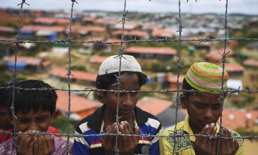 Refugiados Rohingya oram em cerimônia que relembra um ano do ataque militar que provocou fuga em massa de Myanmar para Bangladesh Foto: DIBYANGSHU SARKAR / AFP
