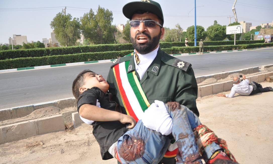 Membro do Corpo de Guardas Revolucionários do Irã carrega uma criança ferida no ataque a uma parada militar em 22 de setembro de 2018 em Ahvaz, no Sudoeste do Irã Foto: BEHRAD GHASEMI / AFP