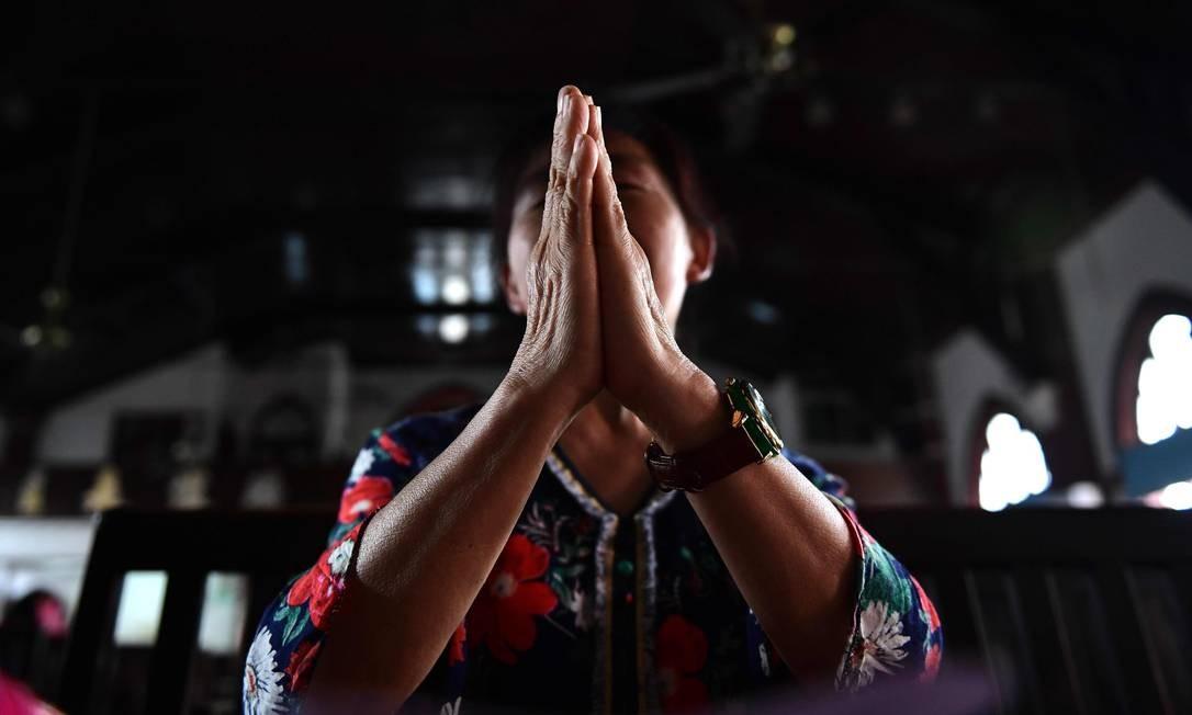 Fiel reza em igreja na cidade chinesa de Wuhan: Vaticano passou a reconhecer alguns bispos nomeados pelo governo chinês Foto: AFP/NICOLAS ASFOURI