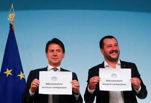 Primeiro-ministro italiano, Giuseppe Conte, e ministro do Interior, Matteo Salvini, levantam papeis em que se lê