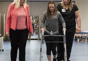 Kelly Thomas, de 23 anos, que perdeu os movimentos voluntários das pernas após acidente de carro, anda observada pelas terapeutas e apoiada em um andador: capacidade recuperada quando o estimulador implantado na sua coluna está ligado Foto: Divulgação/Tom Fougerousse/Universidade de Louisville