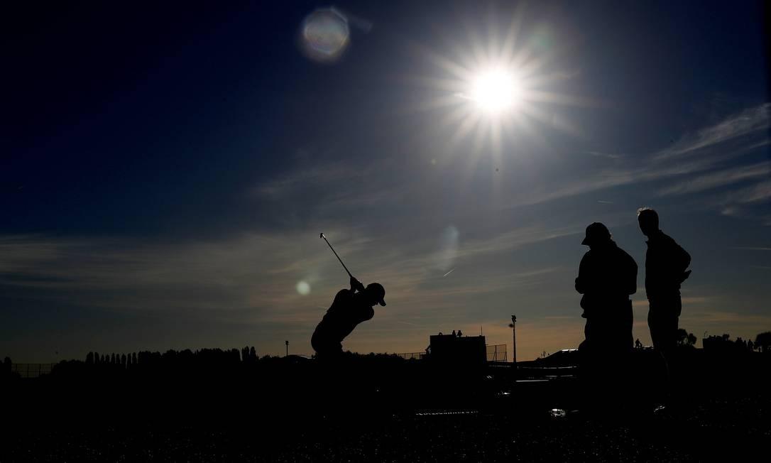 Jogadores de golfe treinam durante o fim de tarde em Guyancourt, França. Foto: PAUL CHILDS / REUTERS