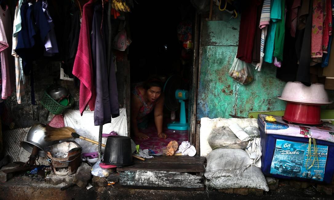 Uma mulher é fotografada dentro de sua casa em Bangkok, Tailândia. Foto: ATHIT PERAWONGMETHA / REUTERS