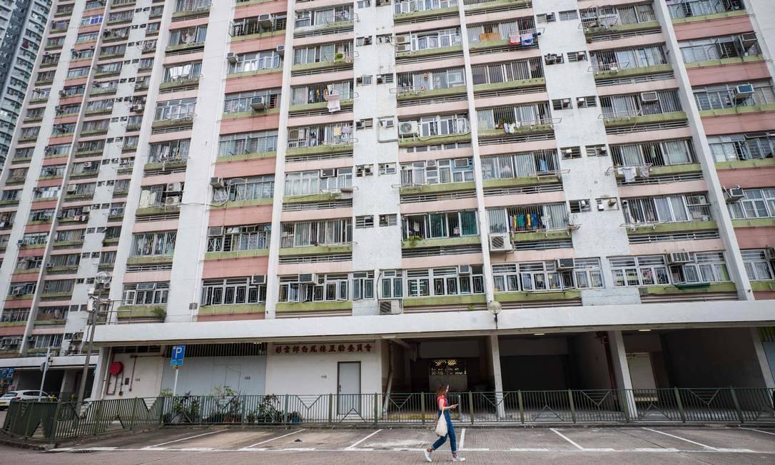 Mulher passa em frente à entrada de prédio no conjunto habitacional de Choi Wan, em Hong Kong, onde morava o homem que teve primeiro caso diagnosticado do vírus de roedores em humanos Foto: AFP/ANTHONY WALLACE