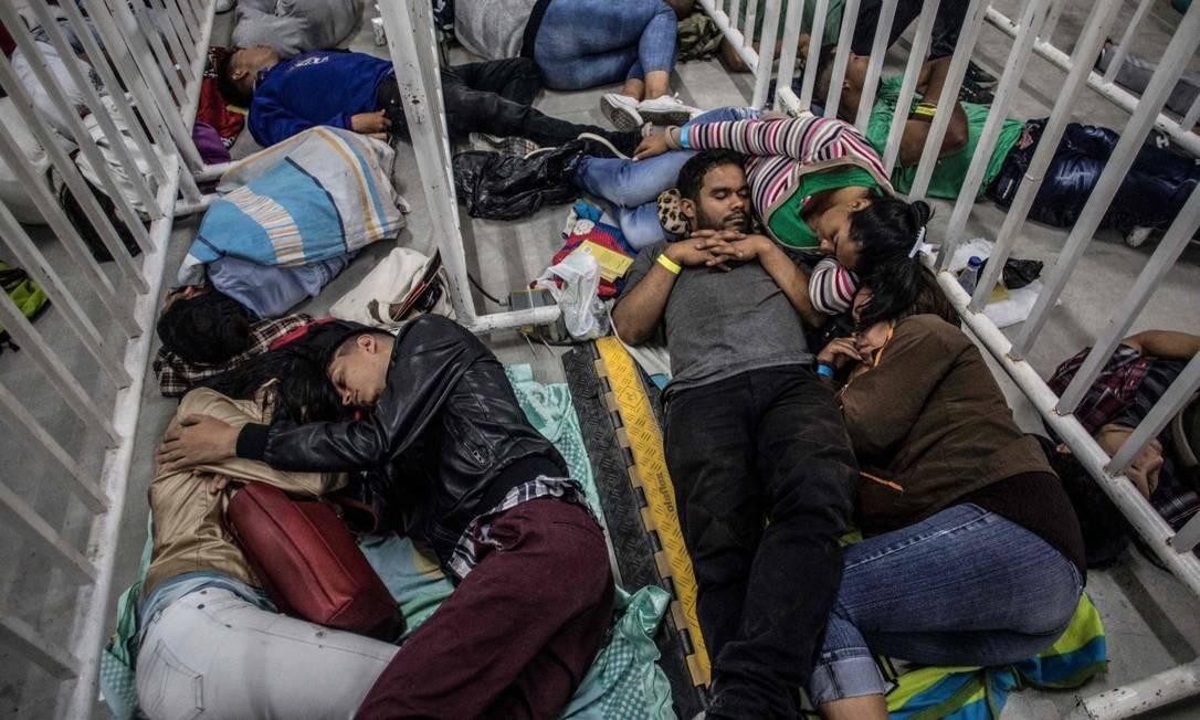 Imigrantes venezuelanos dormem na fila para comparecer a feira de empregos em Medellín, na Colômbia Foto: JOAQUIN SARMIENTO / AFP