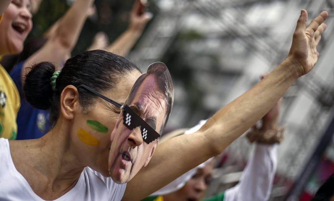 Apoiadora usa máscara de Jair Bolsonaro durante ato em São Paulo Foto: MIGUEL SCHINCARIOL / AFP