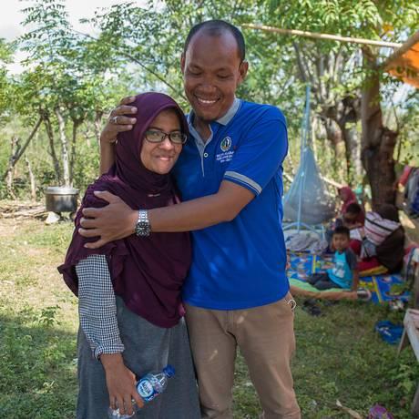 Azwan abraça Dewi Prasasti em frente da casa onde moram em Palu, na Indonésia Foto: BAY ISMOYO / AFP