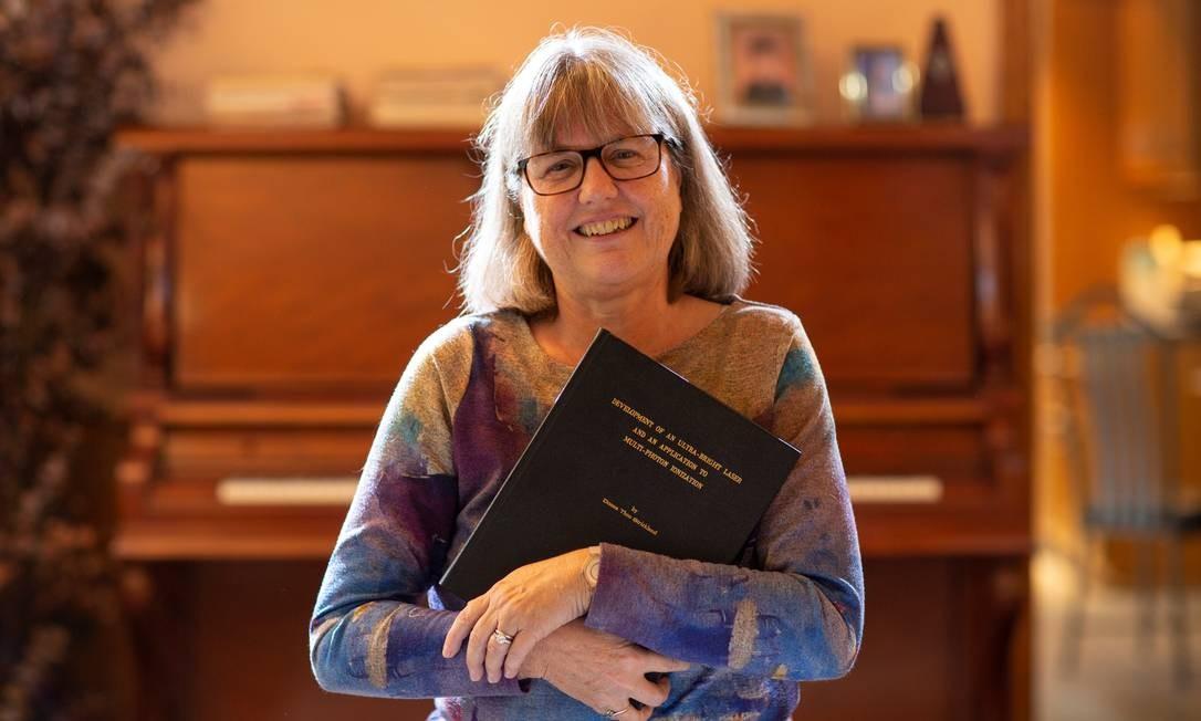 Donna Strickland, professora da Universidade de Waterloo, no Canadá, posa com o artigo baseado em sua tese de doutorado que lhe rendeu o Prêmio Nobel de Física de 2018 Foto: REUTERS/PETER POWER