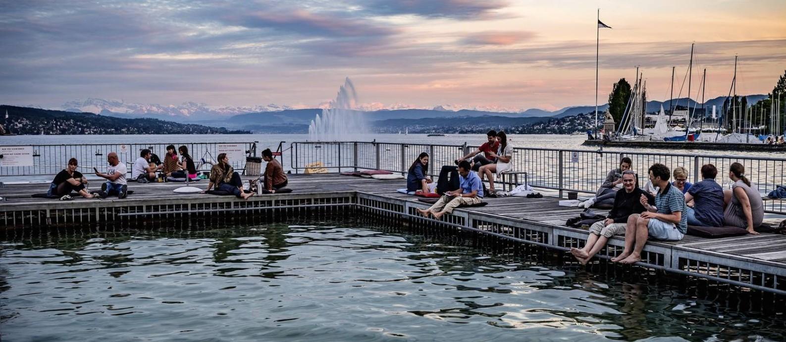 Uma das piscinas públicas de Zurique, onde as pessoas ficam até tarde no verão, com a neve dos Alpes Suíços ao fundo Foto: Alex Buschor / Divulgação