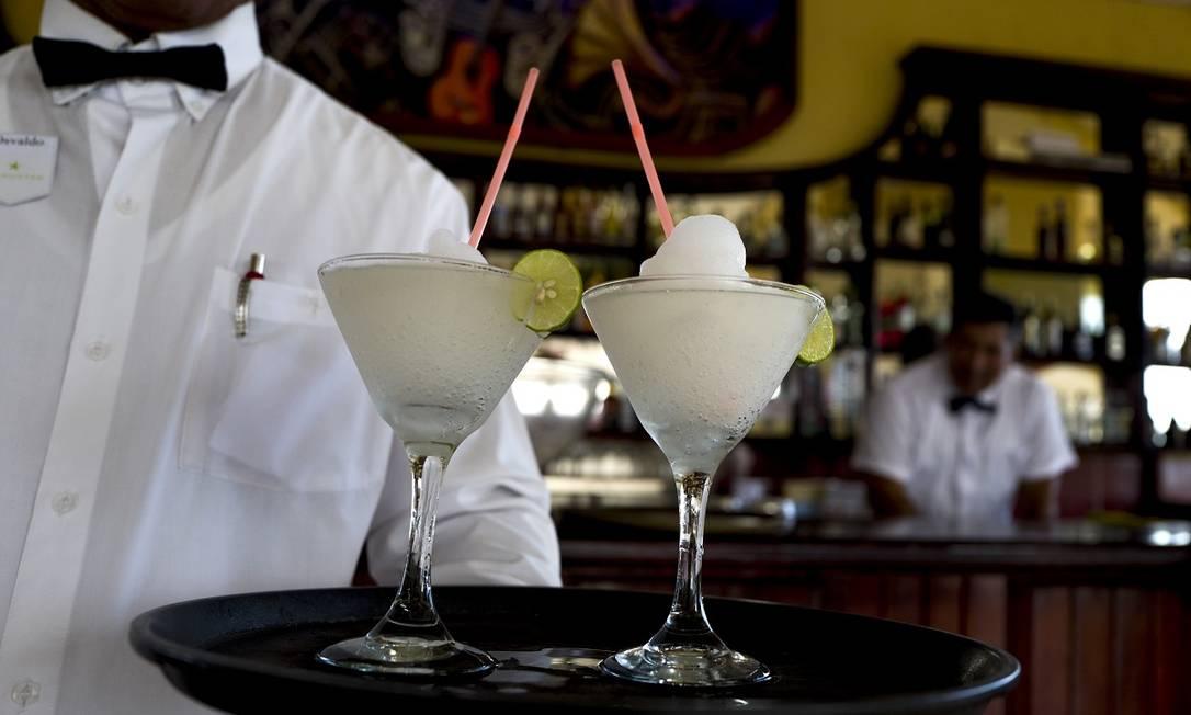 Garçom serve dáiquiris, clássico drinque cubano, feito com rum, no bar do Hotel Casa Granda, em Santiago de Cuba Foto: Eliana Aponte Tobar / The New York Times