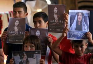Crianças yazidis mostram fotos e o livro de Nadia Murad, ganhadora do Nobel da Paz de 2018 Foto: ARI JALAL / REUTERS