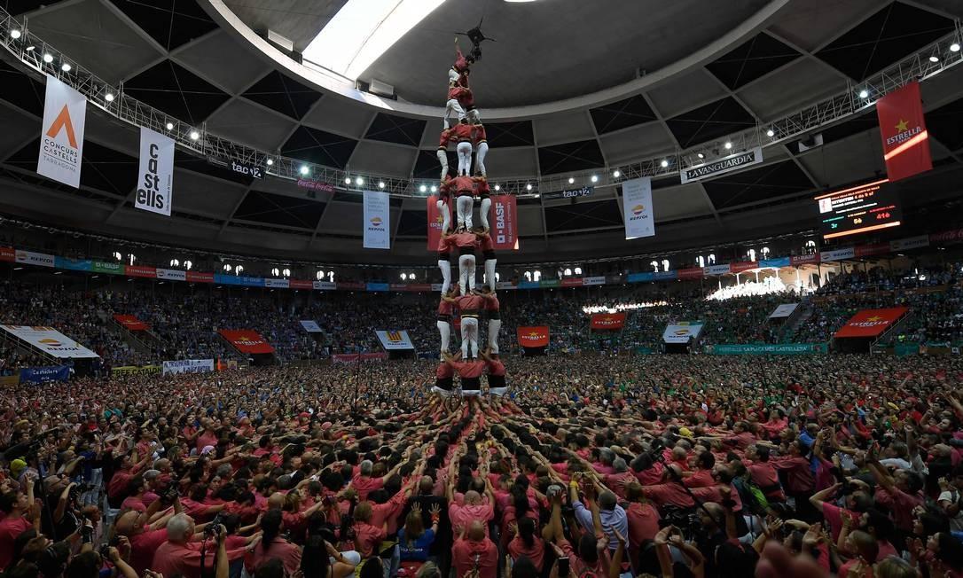 Essas torres, construídas tradicionalmente em festivais na Catalunha, reúnem várias equipes que tentam construir e desmontar uma estrutura de torre humana Foto: LLUIS GENE / AFP