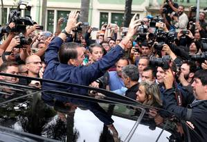 Jair Bolsonaro é saudado por militantes ao chegar em sua zona eleitoral, em Deodoro, na Zona Oeste do Rio; ele estava acompanhado de seguranças e usava um colete à prova de balas Foto: RICARDO MORAES / REUTERS