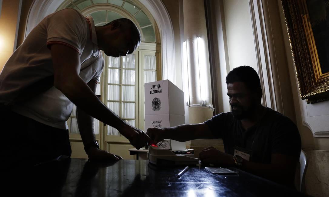 Eleitor é ajudado por mesario a usar a biometria na zona eleitoral na Camara de Vereadores Foto: Antonio Scorza / Agência O Globo