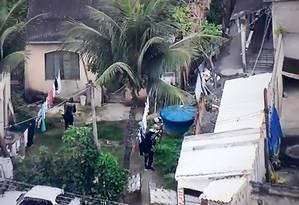 Milicianos uniformizados aparecem inavadindo residências na Favela do Rola Foto: Reprodução/TV Globo