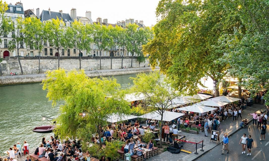 Mesas e cadeiras se espalham ao longo do Rio Sena, em Paris, perto da embarcação Peniche Marcounet Foto: Jo Han Pai / The New York Times
