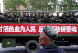 Um homem uigur observa tropas paramilitares em Urumqi, capital de Xinjiang, numa ação antiterrorismo Foto: CHINA STRINGER NETWORK / REUTERS