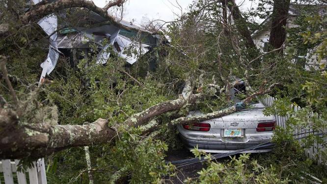 Uma árvore cai sobre uma casa e um carro após passar em Panama City Foto: JOE RAEDLE / AFP