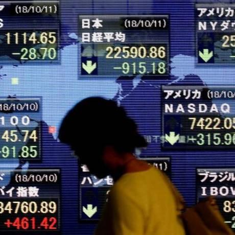 Uma mulher passa em frente ao painel eletrônico mostrando os índices do mercado de ações de vários países em Tóquio Foto: Reuters