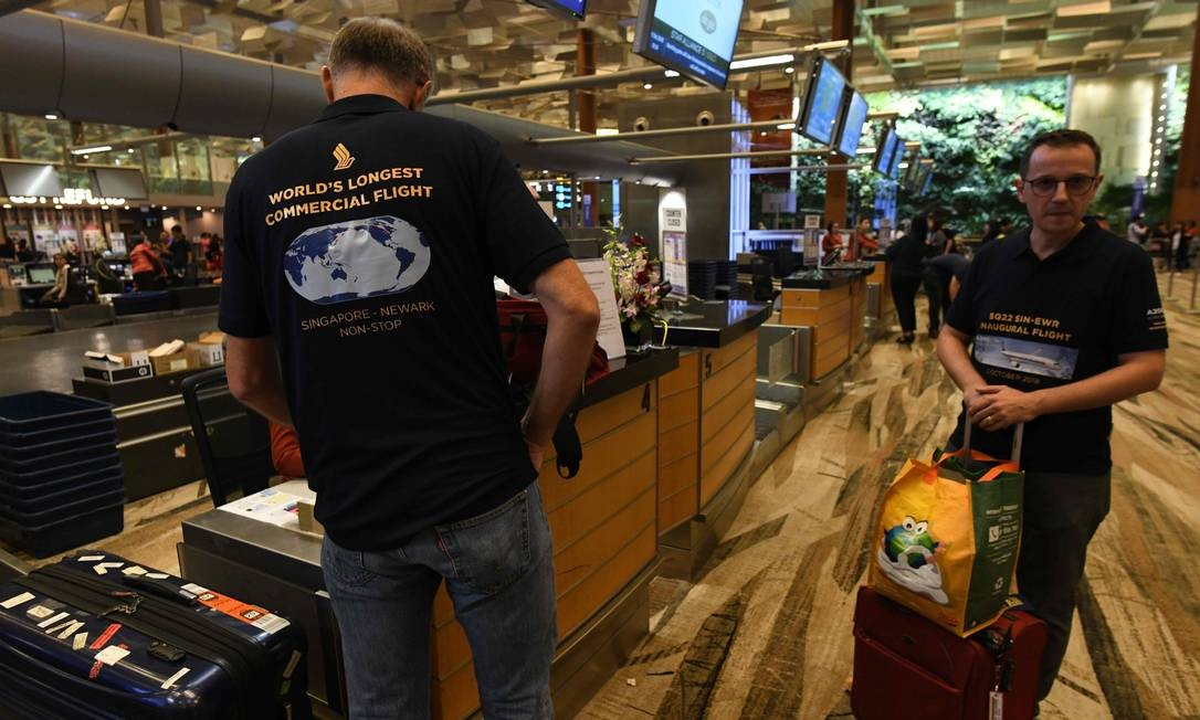 Passageiros do voo SQ22, da Singapore Airlines, o mais longo do mundo, entre Cingapura e Nova York, usam camisas comemorativas à viagem inaugural no aerporto Changi Foto: ROSLAN RAHMAN / AFP