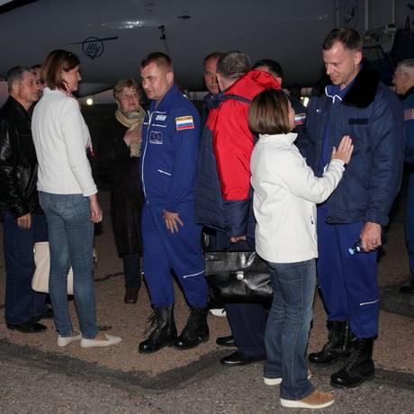 O cosmonauta Alexey Ovchinin, ao centro, e o astronauta Nick Hague, à direita, se encontram com familiares após o incidente com a Soyuz Foto: HANDOUT / REUTERS