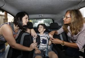 Eliane ajeita o cinto da cadeirinha em um menino Foto: Marcos Ramos / Agência O Globo
