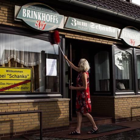 Katrin Robben limpa a entrada de uma cervejaria em Handorf-Langenberg, na Alemanha. Para salvar o lugar, os moradores se tornaram sócios, em forma de cooperativa Foto: LENA MUCHA / NYT