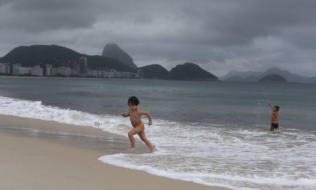 Apesar do mau tempo, crianças brincam no mar de Copacabana Foto: Marcia Foletto / Marcia Foletto
