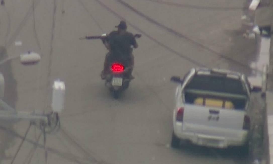 Homem armado com fuzil circula em moto por rua da Cidade de Deus Foto: Reprodução / Bom Dia Rio