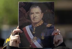 Um apoiador do ditador chileno Augusto Pinochet segura uma foto dele no aniversário de 30 anos do plebiscito que acabou com sua ditadura Foto: CLAUDIO REYES / AFP-5_10_18