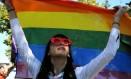 Mulher segura a bandeira que representa lésbicas, gays, bissexuais e transgêneros Foto: LAURA HASANI / REUTERS