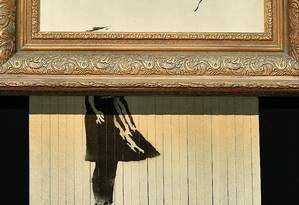 """""""Óóóó!"""", fizeram os presentes na Sotheby's, em Londres, quando, por controle remoto, um triturador retalhou metade da obra Menina com balão, de Banksy. Após a autodestruição, ela foi rebatizada de O amor está no lixo Foto: BEN STANSALL / AFP"""