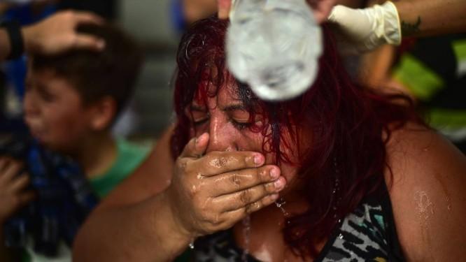 Mulher que integra caravana é socorrida após embate entre migrantes e policiais na fronteira entre Guatemala e México Foto: PEDRO PARDO / AFP
