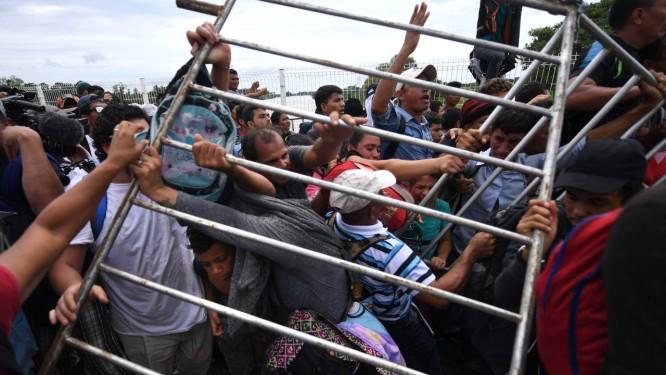 Migrantes hondurenhos removem barreiras para chegar ao território mexicano, uma etapa-chave; alguns querem ficar no México, e outros almejam chegar aos Estados Unidos Foto: PEDRO PARDO / AFP