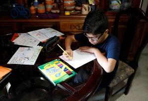 Gabriel Moncada desenha na sua casa, em Caracas, sobre crise que afeta venezuelanos Foto: MARCO BELLO / REUTERS