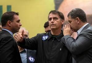 O candidato à Presidência Jair Bolsonaro ao lado do filho Flávio Bolsonaro e do presidente do PSL, Gustavo Bebianno Foto: MAURO PIMENTEL / AFP