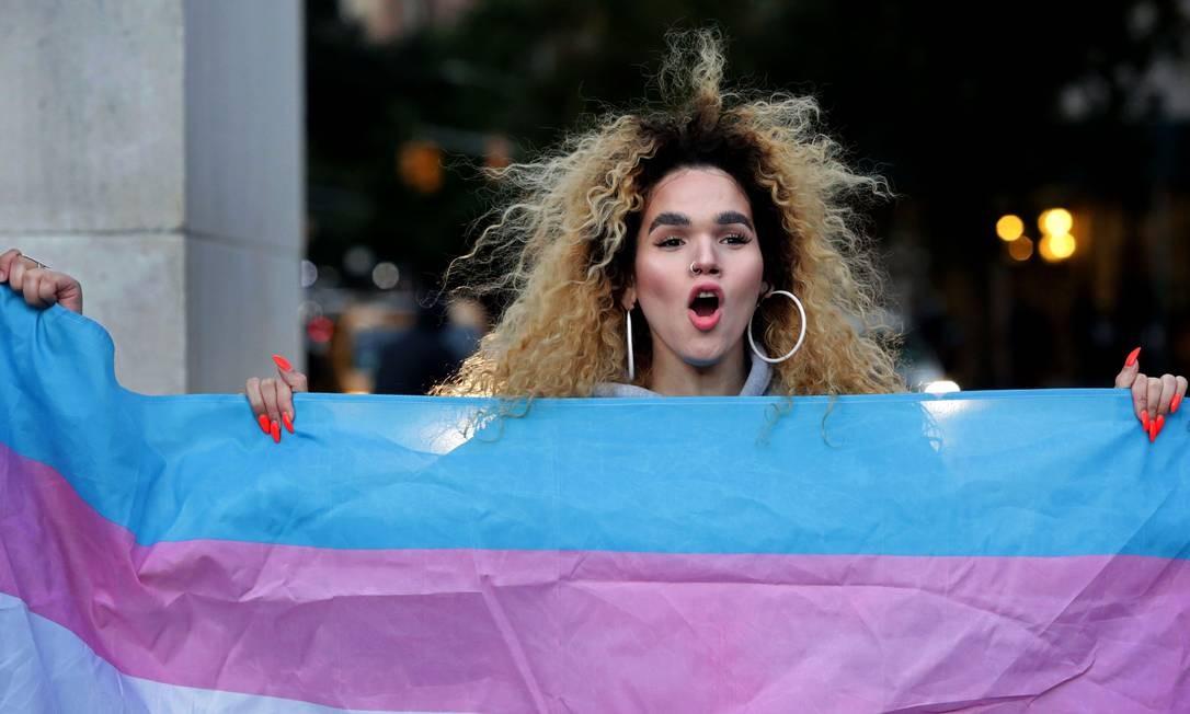 Mulher trans segura a bandeira da comunidade transexual, em Nova York Foto: Yana Paskova / AFP