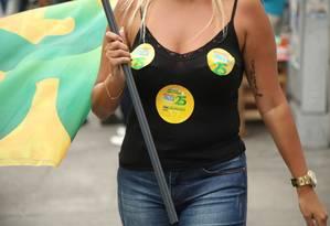Cabo eleitoral usa adesivo com os números de Paes e Bolsonaro, no Largo da Taquara Foto: Bárbara Lopes / Agência O Globo
