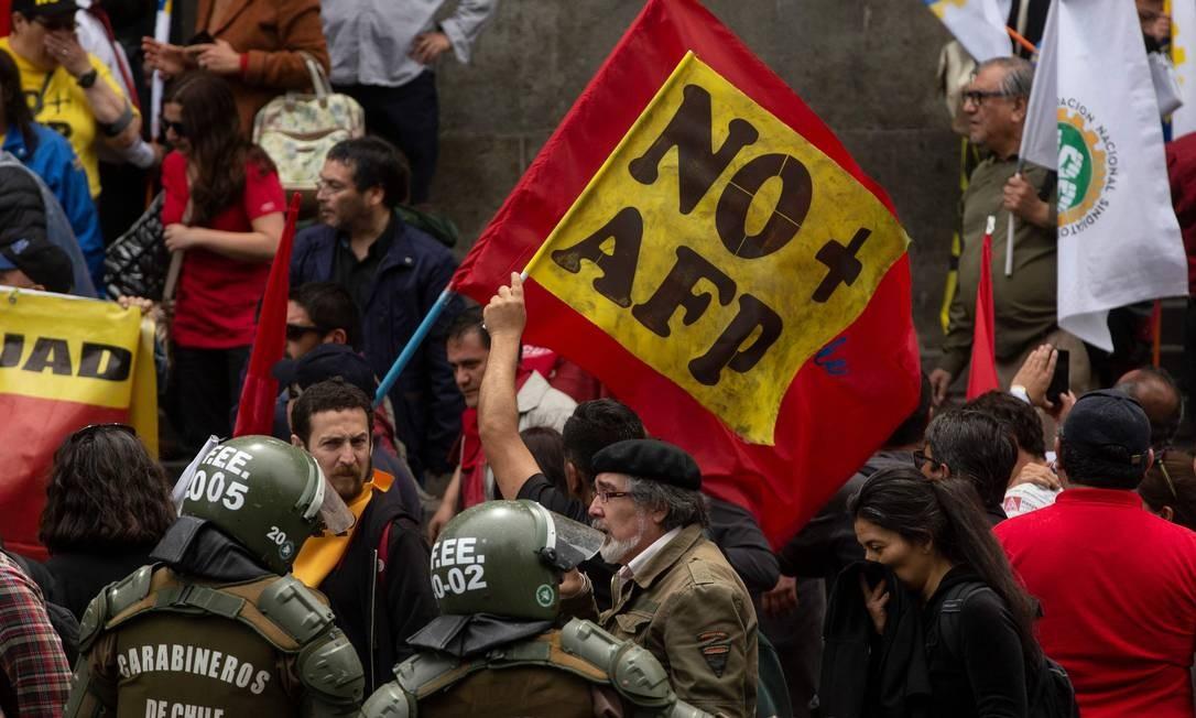 Trabalhadores chilenos enfrentam a polícia durante um protesto contra as AFPs, as Administradoras de Fundos de Pensões, responsáveis pelo sistema privatizado de aposentadoria no país Foto: CLAUDIO REYES / AFP