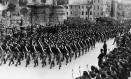 Jovens fascistas na Marcha do Triunfo passam por Mussolini, na Itália, em outubro de 1935 Foto: Topical Press Agency / Getty Images