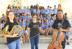 Inovador. Waleska (à esquerda), Natalia Terra e Ronildo Cândido, da Orquestra Sinfônica da UFF, à frente dos alunos do Coluni: primeira turma formada no projeto Foto: Roberto Moreyra